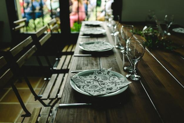 Mesas de madeira com pratos de talheres e copos retroiluminados sem ninguém.