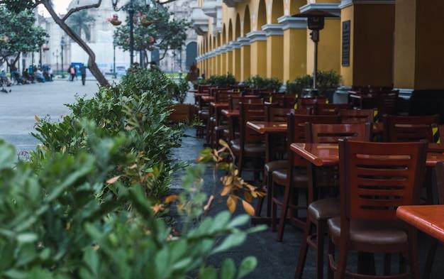 Mesas de restaurante ao ar livre subexpostas no centro histórico de lima, peru, vaso de flores ao redor de mesas de madeira, colunas amarelas