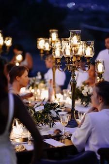 Mesas decoradas com composição floral e castiçais à moda antiga e convidados à noite de comemoração
