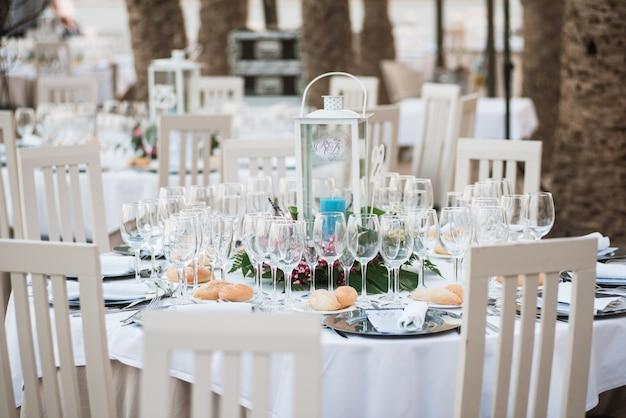 Mesas decoradas para uma recepção de casamento no resort de praia com palmeiras.