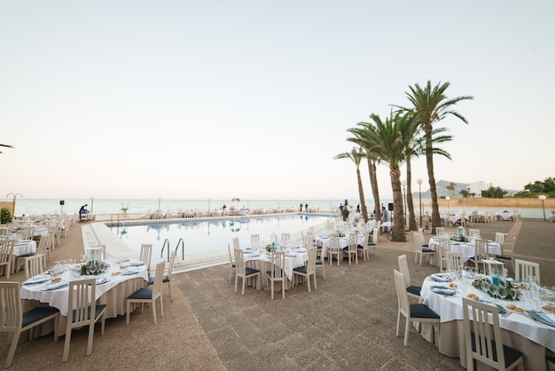 Mesas decoradas para uma recepção de casamento no resort de praia