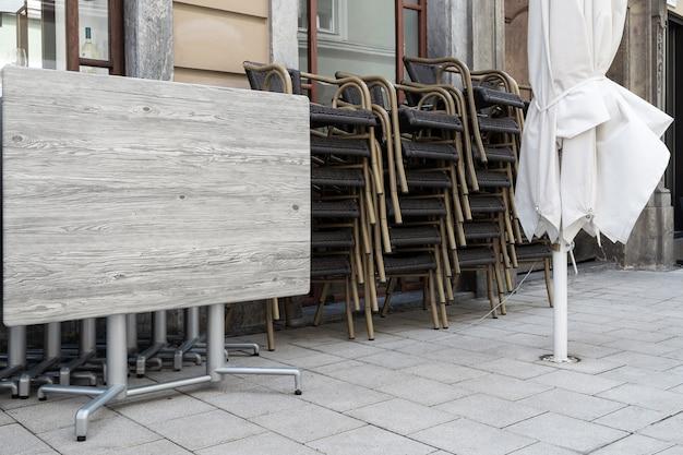 Mesas dobradas e cadeiras de um café da rua estão na calçada.