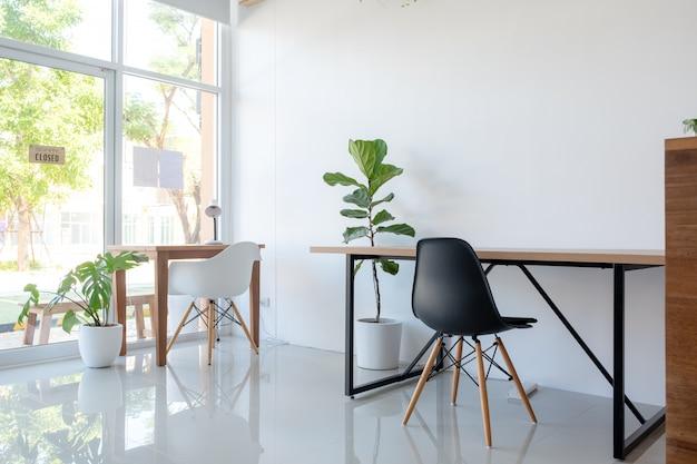 Mesas e cadeiras com árvores decorativas no escritório