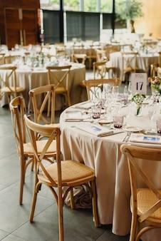 Mesas e cadeiras de madeira dispostas e decoradas em um salão de festas de um hotel