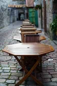 Mesas e cadeiras de madeira em um beco de paralelepípedos com um visual vintage.