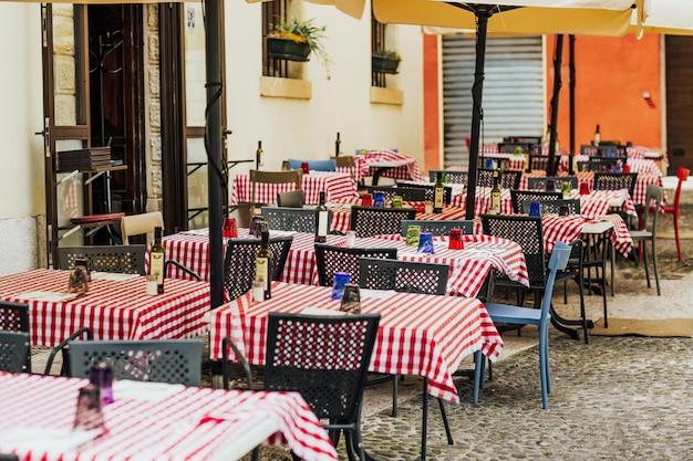 Mesas e cadeiras de restaurante em uma pequena praça na itália.