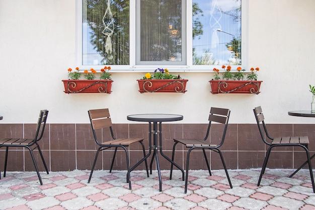 Mesas e cadeiras de vidro e metal em um terraço de verão café pela janela