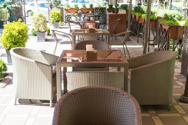 Mesas e cadeiras de vime em um café de verão ao ar livre com canteiros de flores