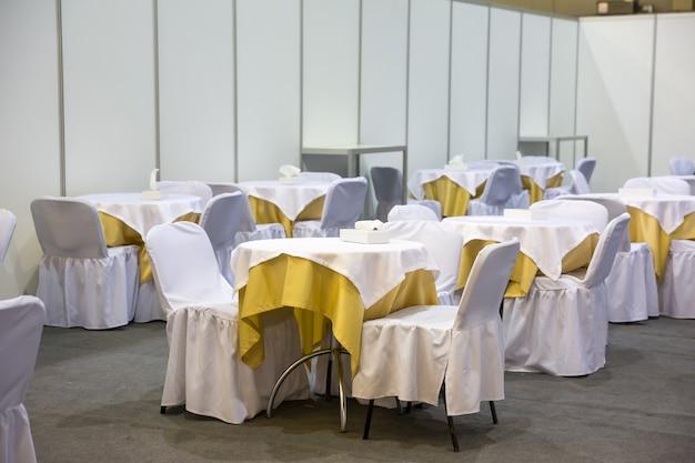 Mesas e cadeiras festivas com toalhas brancas no corredor