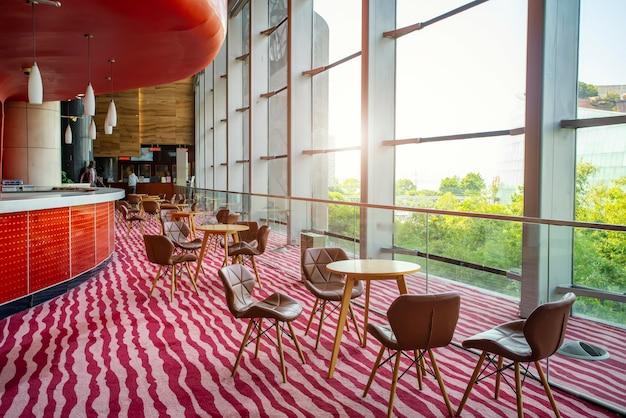 Mesas e cadeiras na área de lazer do lobby do hotel