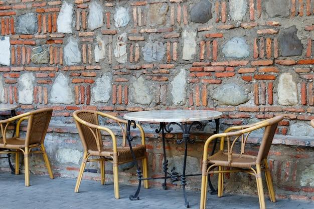 Mesas e cadeiras no café ao ar livre. pátio encostado na parede de pedra
