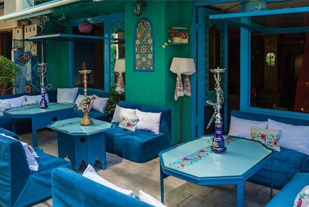 Mesas e sofás azuis com dois narguilés azuis e um amarelo. mesas com narguilé.
