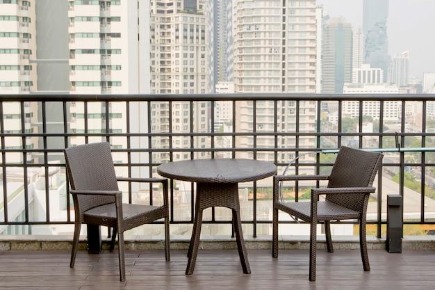 Mesas vazias e cadeiras no terraço com vista para o alto edifício