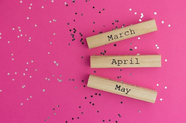 Meses de primavera do calendário de madeira março, abril, maio. fundo rosa com confetes multicoloridos. estilo liso