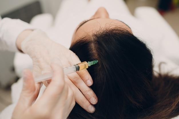 Mesoterapia com agulha. cosmético foi injetado na cabeça da mulher.