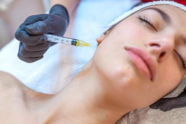 Mesoterapia na testa. tratamento mesoterapia. procedimento de mesoterapia. o cosmetologista médico faz o procedimento de mesoterapia na cabeça da mulher. fortalecer o cabelo e seu crescimento.