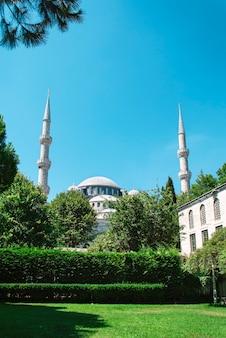 Mesquita azul à distância na praça sultanahmet com grama verde em primeiro plano.