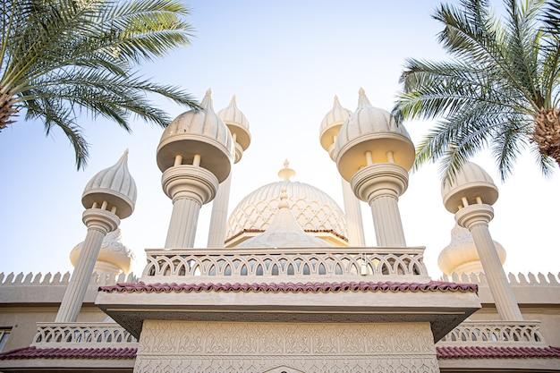 Mesquita islâmica tradicional entre palmeiras em dias ensolarados
