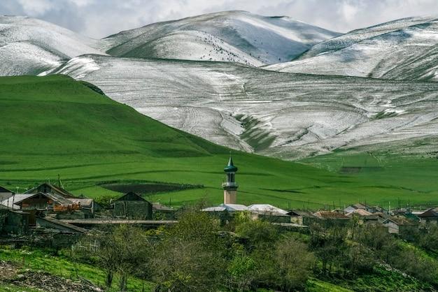Mesquita na vila de verkhniy karanay contra o pano de fundo de colinas verdes e montanhas cobertas de neve verkhniy karanay daguestão rússia