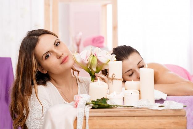 Messeur lindo sentado atrás de velas acesas, segurando flores concursos