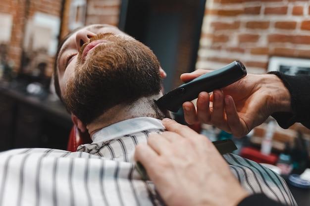 Mestre afiando sua barba com um aparador elétrico
