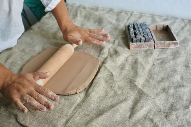 Mestre artesão rola argila na mesa