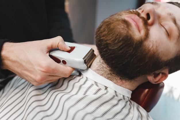 Mestre barbeiro usa barbeador elétrico