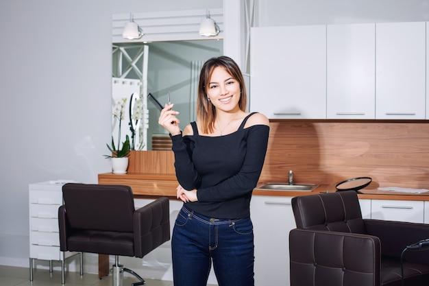 Mestre cabeleireira jovem mulher bonita com sorriso e ferramentas profissionais em um salão de beleza