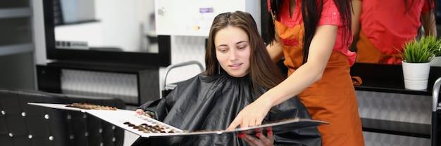 Mestre cabeleireiro ajuda cliente a escolher a cor da tintura de cabelo