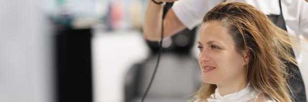 Mestre cabeleireiro seca o cabelo com secador de cabelo para um cliente no salão de beleza