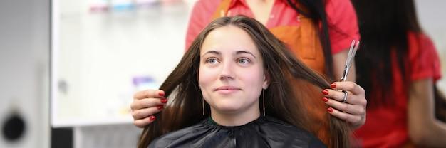 Mestre cabeleireiro segurando o cabelo da cliente no salão de beleza