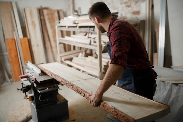 Mestre carpinteiro serra a placa na máquina na oficina