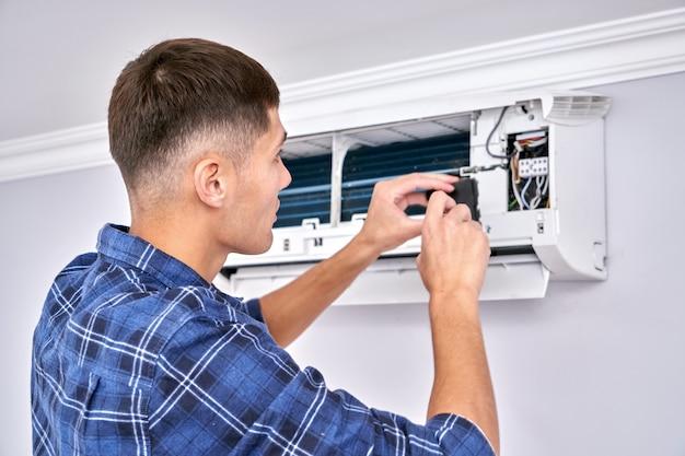 Mestre caucasiano do sexo masculino com camisa azul limpa filtros, instala e conserta ar-condicionado em ambientes internos