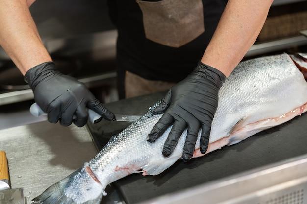 Mestre chef com luvas pretas de higiene, limpeza e preparação de um enorme salmão fresco. conceito de comida e cozinha