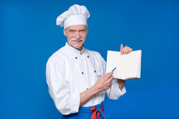 Mestre chef idoso isolado na parede azul, com seu bloco de notas, procurando uma nova receita