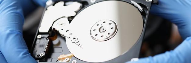 Mestre com luvas segurando o disco rígido do computador close