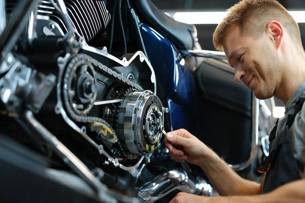 Mestre consertando motocicleta na oficina usando uma chave inglesa