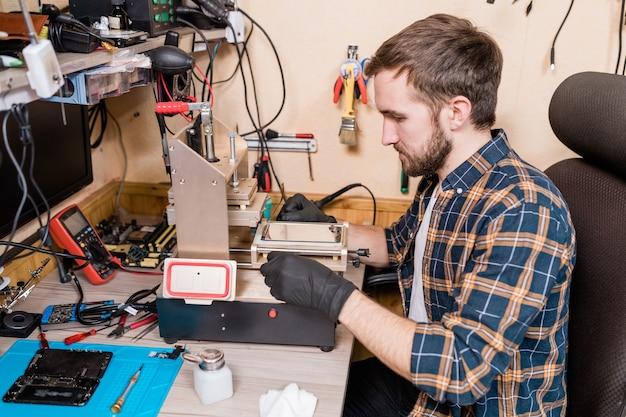 Mestre contemporâneo em serviço de conserto de gadgets em luvas de proteção usando equipamentos especiais durante a reparação de smartphones