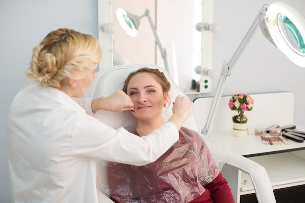Mestre corrige maquiagem, dá forma e fio arranca as sobrancelhas em um salão de beleza. cuidado profissional para o rosto
