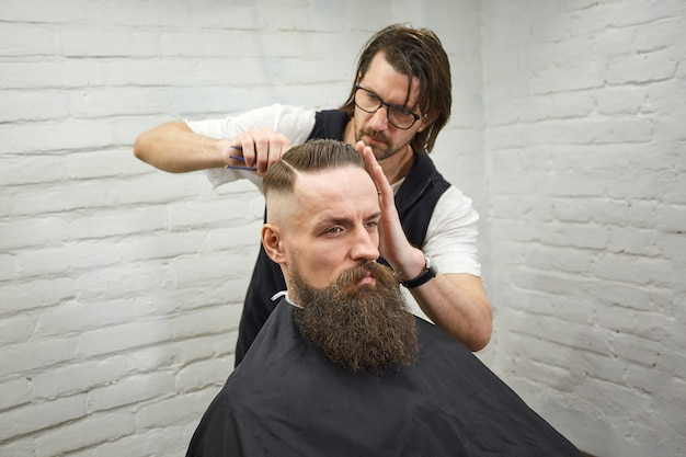 Mestre corta cabelo e barba de homens na barbearia, cabeleireiro faz penteado para um jovem
