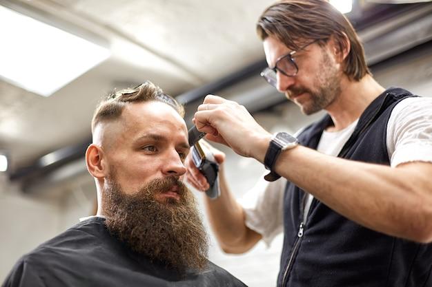 Mestre corta cabelo e barba de homens na barbearia, cabeleireiro faz penteado para um jovem.