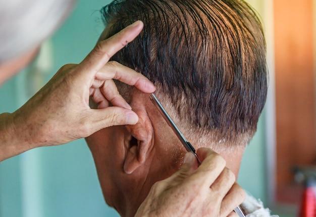 Mestre corta cabelo e barba de homens na barbearia, cabeleireiro faz penteado