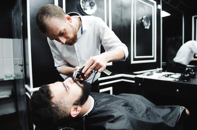 Mestre corta cabelo e barba de homens na barbearia, cabeleireiro