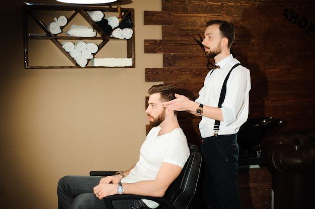 Mestre corta cabelo e barba de homens na barbearia