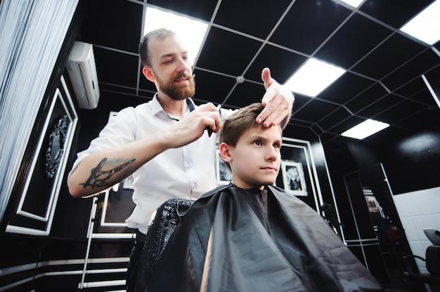 Mestre corta o cabelo de um menino na barbearia