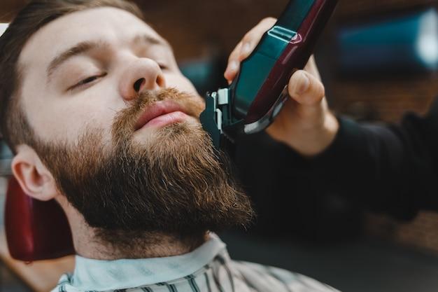 Mestre de barbeiro corta a barba para um cliente