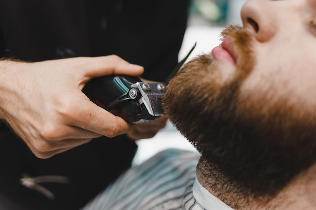 Mestre de barbeiro corta uma barba para um close-up do cliente