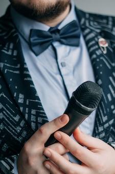 Mestre de cerimônias com microfone. homem com barba e close-up de gravata borboleta. terno de negócios, fala e fala, talk show, porta-voz do seminário.