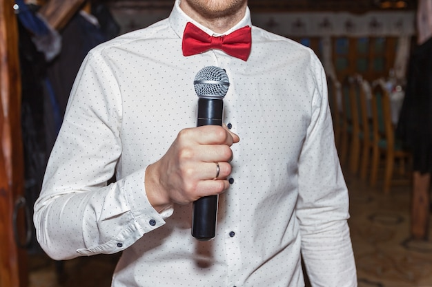 Mestre de cerimônias em uma camisa branca e com uma borboleta vermelha segurando um microfone na mão, mestre de cerimônias com microfone