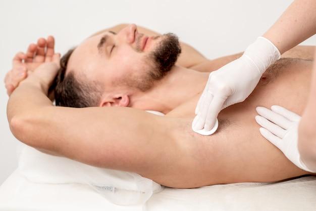 Mestre de depilação limpando a axila masculina